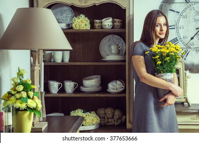 happy beautiful young fashion caucasian model in grey dress and fashion makeup and tall brown hair posing with yellow flowers, smiling and looking at camera in provence design interior.
