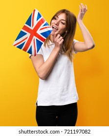 Happy Beautiful young girl holding an United Kingdom flag on yellow background