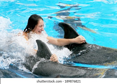 Happy beautiful young girl laughs and swims with dolphins in blue swimming pool on a clear sunny day