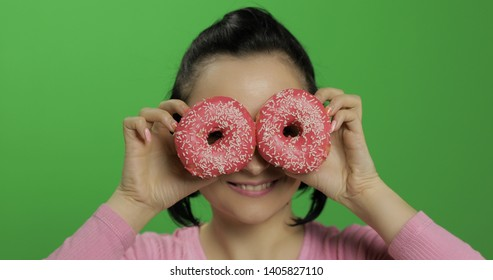 Happy beautiful young girl on a chroma key background having fun with donuts. Cute woman in a pink shirt posing with donuts. Making faces