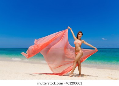 Happy beautiful young girl in pink bikini with waving in the wind pink fabric on a tropical beach. Blue sea in the background. Summer vacation concept.