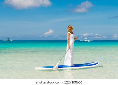 Happy beautiful young girl in a white dress with paddle board on a tropical beach. Blue sea in the background. Summer vacation concept.