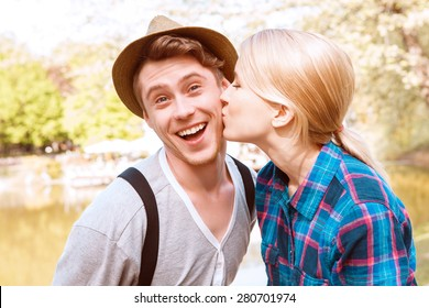 So happy. Beautiful young lady giving kiss to cheek to his boyfriend in park on background of lake.