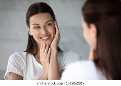 Happy beautiful young lady touching face look in bathroom mirror, happy pretty woman enjoy healthy soft moisturized hydrated skin, facial skincare rejuvenation moisture spa everyday treatment concept