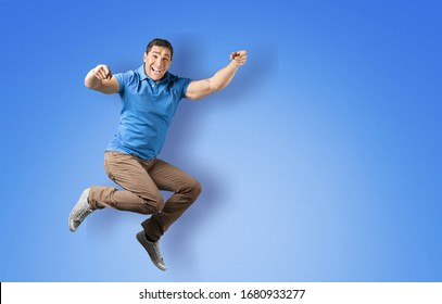 Happy beautiful young man jumping on the colored background