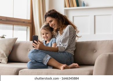 Happy beautiful young mother resting on couch with little preschool daughter, showing funny cartoons on mobile phone. Smiling affectionate family of two posing for smartphone selfie shot on sofa.