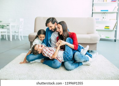 Happy beautiful young parents are smiling, hugging and playing with them kids at home together