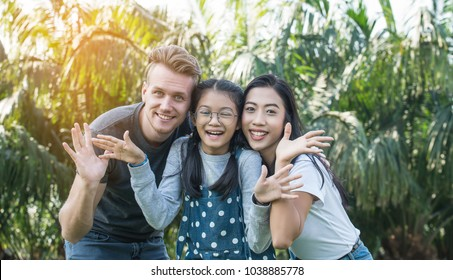 Happy beautiful young parents and their cute daughter hugging in public park,Happy parents kissing daughter,Family holiday vacation togetherness kiss love,Children and people concept - family,Relation