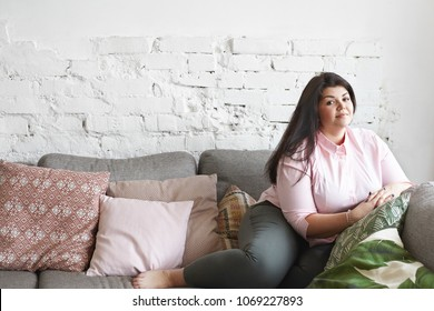 d66ff380c3785 Happy beautiful young plus size female with loose black hair wearing large  pink shirt and skinny