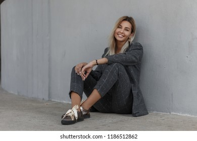 Happy beautiful young stylish model girl with a smile in a gray vintage suit with a stylish jacket and trousers smiling and sitting near the wall