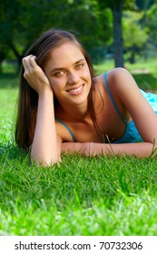 happy beautiful young teenage woman with long brunette hair lying and dreaming on green grass on the farm in bright sunshine
