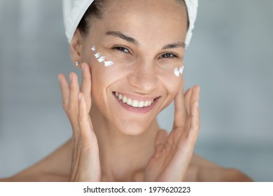 Happy beautiful young woman applying moisturizing nourishing cream with collagen on dry skin at eyes, massaging face with fingers, smiling. Skincare, treatment concept. Close up portrait - Shutterstock ID 1979620223