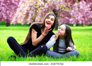 Happy beautiful young woman in blossom park with trees and flowers.