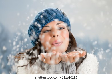Happy beautiful young woman blowing snowflakes from her hands in a winter day