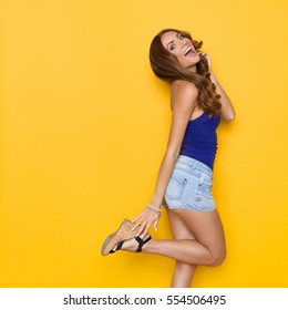 Happy beautiful young woman in blue shirt and jeans shorts standing on one leg and shouting. Three quarter length studio shot on yellow background.