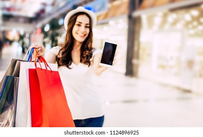 Happy beautiful young woman in casual clothes with shopping bags showing blank phone screen in hand on shopping center background. Cheerful buyer. Day of discounts. Online Shopping