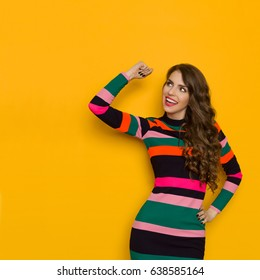 Happy beautiful young woman in colorful vibrant striped dress with long sleeves is holding arm raised, smiling and looking away. Three quarter length studio shot on yellow background.
