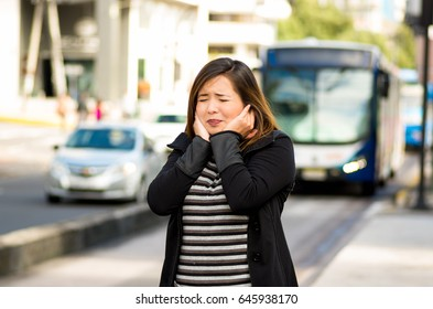 Happy beautiful young woman covering her ears with both hands on the street in the city with sound pollution with a blurred bus behind, city background