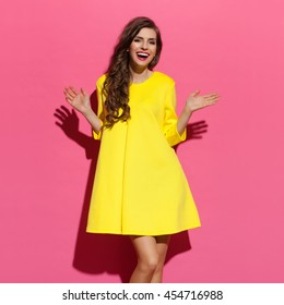 Happy beautiful young woman with curly long brown hair posing in yellow dress. Three quarter length studio shot on pink background.