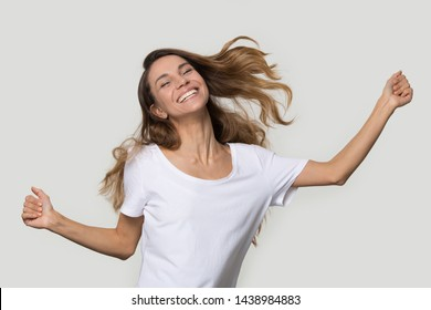 Happy beautiful young woman dancing, attractive female feeling excited, jumping, having fun, emotional girl enjoying music, celebrating win, success, funny activity, isolated on studio background