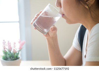 Happy beautiful young woman drinking water. female model holding transparent glass in her hand. Closeup. Focus on the arm