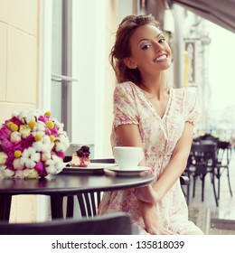 Happy beautiful young woman drinking coffee. Outdoors