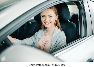 Happy beautiful young woman driver sitting in new car