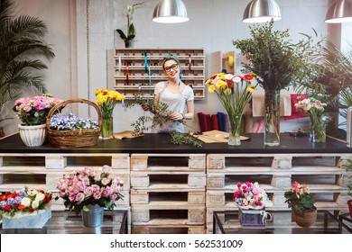 Happy beautiful young woman florist in glasses standing in flower shop