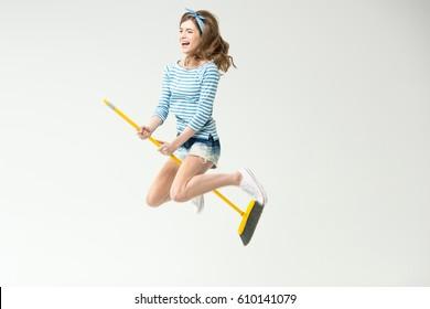 Happy beautiful young woman flying on broom isolated on grey