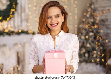 Happy beautiful young woman holding a gift box with hands on Christmas background with lights. Happiness concept, closed eyes, wide smile showing teeth. Making a wish on Christmas eve.