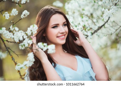 Happy beautiful young woman with long black healthy hair enjoy fresh flowers and sun light in blossom park at sunset.