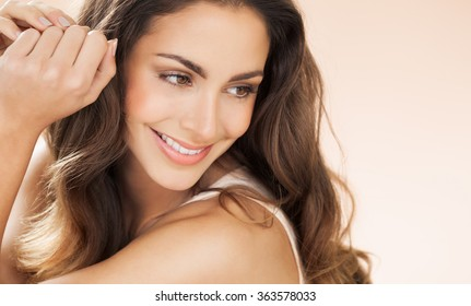 Happy beautiful young woman with long hair smiling over beige background. Fashion and beauty concept in studio.