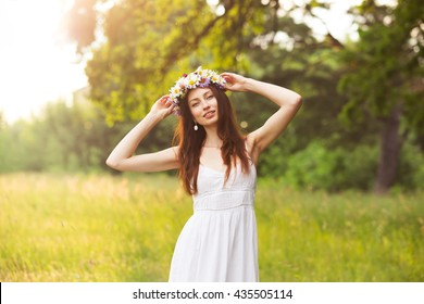 happy beautiful young woman in a long white dress at sunset with a wreath on his head