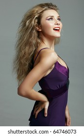 happy beautiful young woman with long blond hair wearing a purple evening dress.