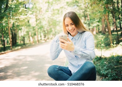happy beautiful young woman with mobile smiling on nature in green