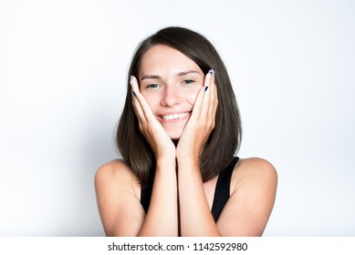happy beautiful young woman pleasantly surprised, isolated studio photo on gray background