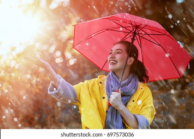 Happy beautiful young woman with red umbrella under the autumn shower. Girl is wearing yellow raincoat and enjoying rainfall.