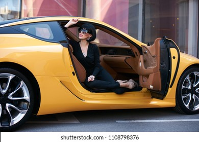 Happy beautiful young woman sitting in a yellow sports car on beautiful sunny summer day. Business Woman lady in black suit and sunglasses sitting in luxury supercar