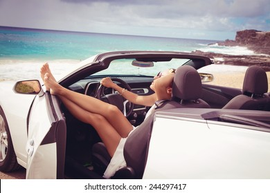Happy beautiful young woman sitting in a sports car on beautiful sunny summer day. Sexy woman's legs showing out of the car, enjoying freedom feeling happy on the Hawaiian beach.