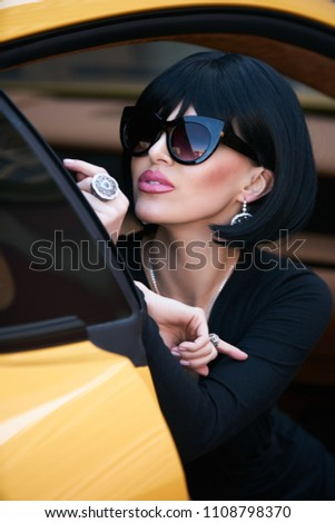 Happy beautiful young woman sitting in a yellow sports car on beautiful  sunny summer day. Business Woman lady in black suit and sunglasses sitting  in luxury ... 9ea04925e