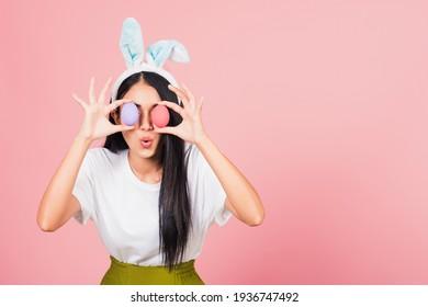Happy schöne junge Frau, die mit Kaninchenähren lächelt, die bunte Ostereier halten Vorderaugen, thailändisches Weibchen mit sonnigem Ohr, Osterei auf Auge, Studioaufnahme einzeln auf rosafarbenem Hintergrund