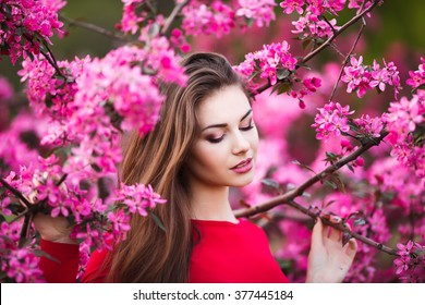 Happy beautiful young woman in spring blossom park.