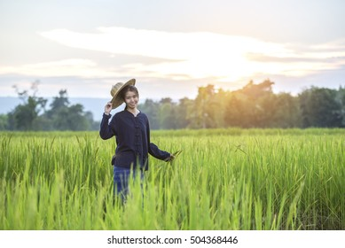Happy beautiful young woman standing in the rice field.