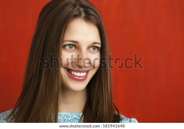 Happy beautiful young woman in a turquoise dress on red background. Studio portrait