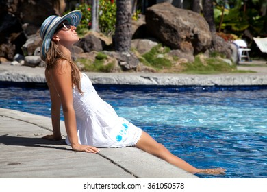 Happy beautiful young woman in white dress enjoying swimming pool and exotic summer luxury vacation. Tourism Concept.