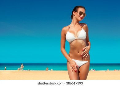 happy beautiful young woman in white bikini and sunglasses posing on the beach sea