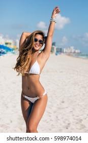 happy beautiful young woman in white bikini and sunglasses posing on the beach sea