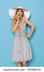 Happy beautiful young woman in white dotted summer dress and sun hat is holding hand on chin, shouting and looking at camera. Three quarter length studio shot on turquoise background.