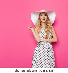 Happy beautiful young woman in white dotted summer dress and sun hat is pointing, looking at camera and talking. Three quarter length studio shot on pink background.