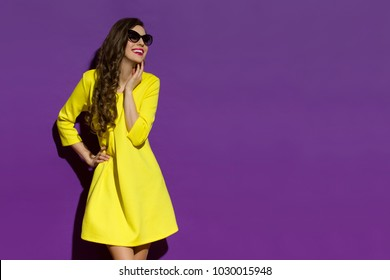 Happy beautiful young woman in yellow mini dress and sunglasses is looking away and smiling. Three quarter length studio shot on purple background.
